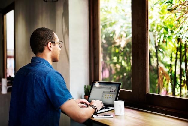 Concetto di collegamento del computer portatile di lavoro della caffetteria dell'uomo