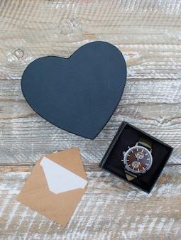 Concetto di compleanno con busta, scatole regalo con orologio su fondo in legno piano laici.