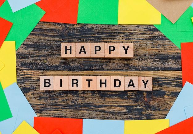 Concetto di compleanno con buste colorate, cubi di legno su fondo in legno piatto laici.