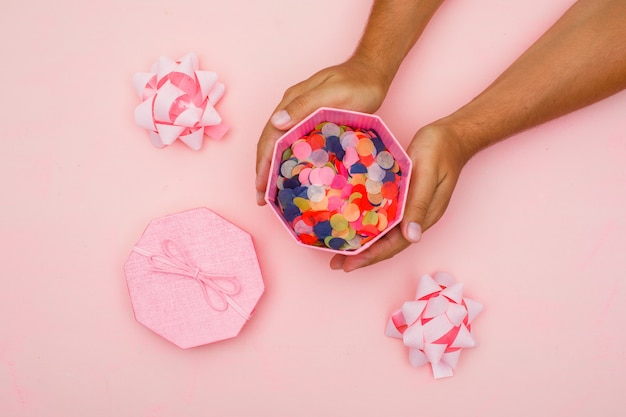 Concetto di compleanno con coriandoli, fiocchi su sfondo piatto rosa laici. mani che tengono confezione regalo.