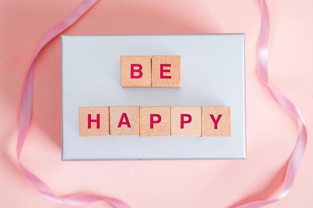 Concetto di compleanno con i blocchi di legno, nastro sulla disposizione piana del fondo rosa e bianco.