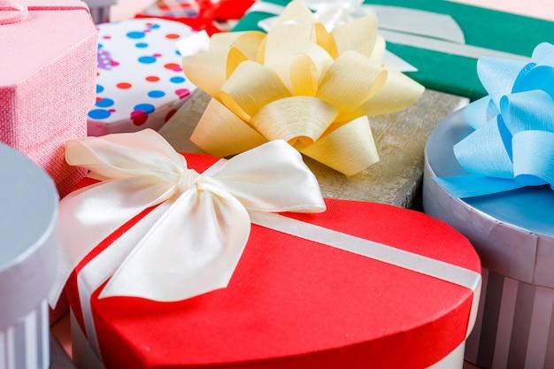 Concetto di compleanno con i contenitori di regalo assortiti sulla vista dell'angolo alto del fondo rosa.