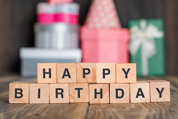 Concetto di compleanno con i contenitori di regalo, cubi di legno sulla vista laterale della tavola di legno.