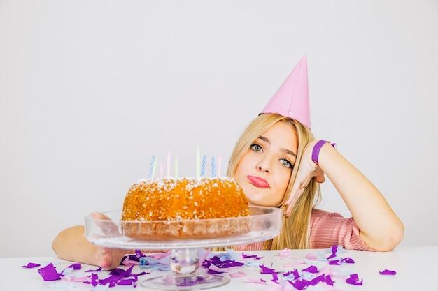 Concetto di compleanno con ragazza annoiata dietro la torta