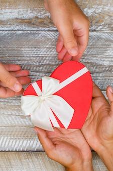 Concetto di compleanno sulla disposizione piana del fondo di legno. mani che danno e ricevono la scatola attuale.