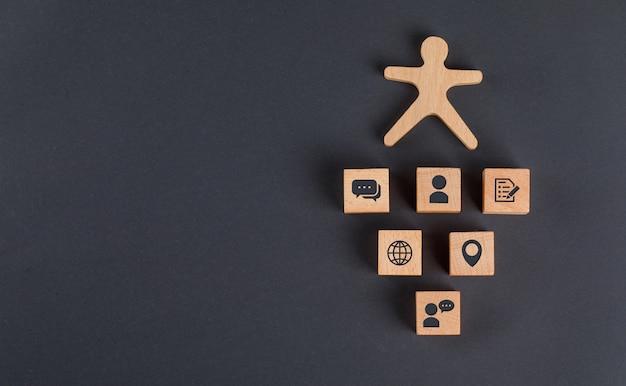 Concetto di comunicazione con le icone sui cubi di legno, figura umana sulla disposizione piana del tavolo grigio scuro.