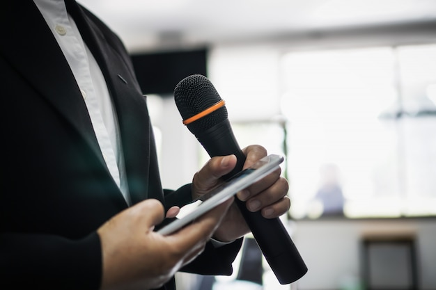 Concetto di conferenza del seminario: mani che tengono gli uomini d'affari che parlano o parlano con i microfoni nella stanza del seminario, parlando per una lezione all'università del pubblico