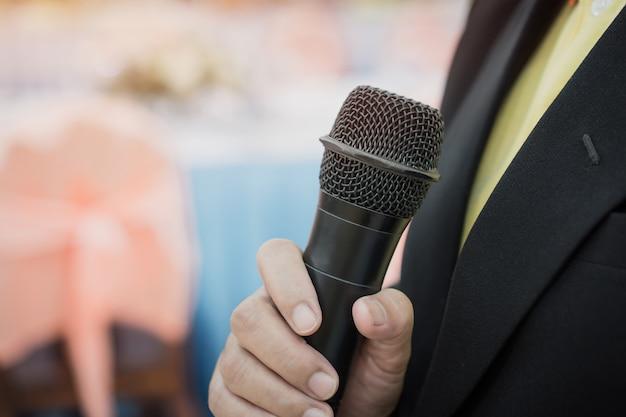 Concetto di conferenza di seminario: passa la gente di affari che tiene i microfoni per discorso che parla