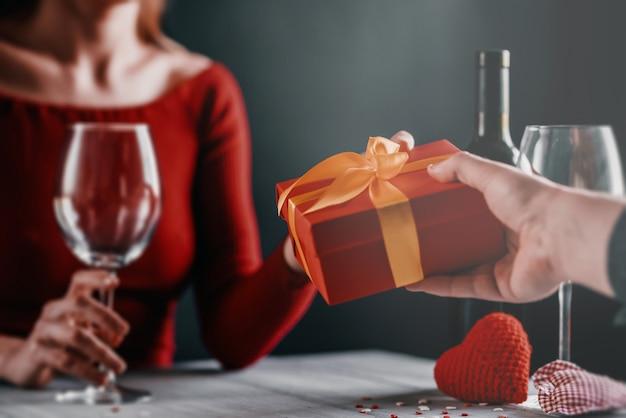 Concetto di congratulazioni per san valentino. coppia al tavolo in un ristorante.