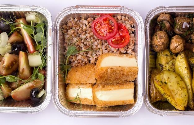 Concetto di consegna a domicilio. primo piano di grano saraceno e formaggio fritto in contenitori