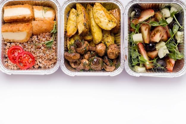 Concetto di consegna a domicilio. su un piatto bianco porridge con verdure e formaggio, insalata e patate con funghi.