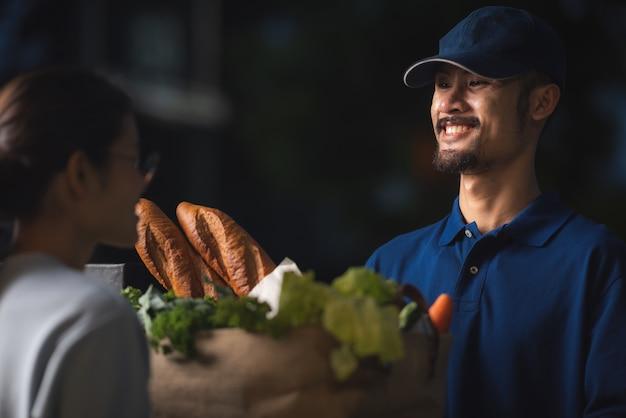 Concetto di consegna di cibo e servizio di corriere, il personale di consegna in uniforme sta attualmente lavorando per consegnare alimenti e prodotti freschi a casa del cliente