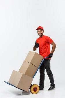 Concetto di consegna - ritratto di bello uomo di consegna afro-americano o corriere spingendo camion a mano con pila di scatole. isolato su sfondo grigio dello studio. copia spazio.