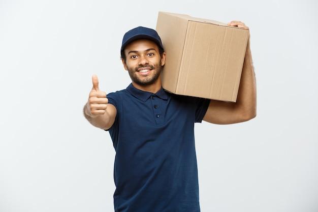 Concetto di consegna - ritratto di uomo felice di consegna dell'afroamericano che punta a presentare un pacchetto di scatola. isolato su sfondo grigio dello studio. copia spazio.