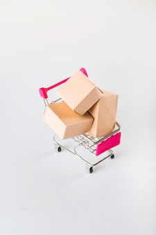 Concetto di consegna su uno sfondo bianco. consegna delle merci, cibo online. carrello in miniatura e copia spazio.