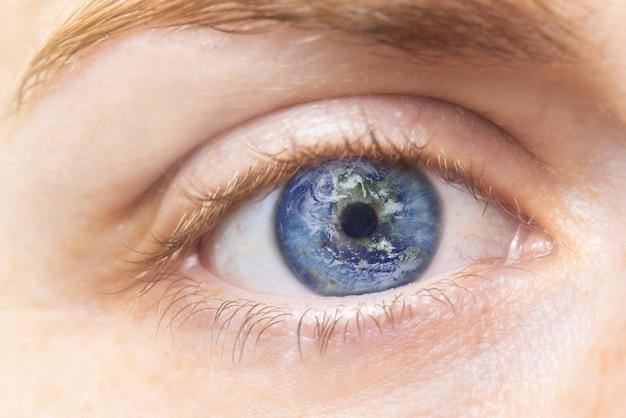 Concetto di conservazione dell'ambiente chiuda sull'immagine dell'occhio della donna con terra in esso. composito creativo di macro eye with earth as iris.