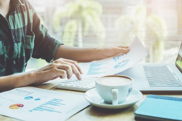 Concetto di contabile. il ragioniere sta premendo il calcolatore per calcolare l'accuratezza del budget di investimento con l'utilizzo di computer portatile e dati del documento per l'analisi.