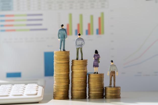 Concetto di contabilità aziendale. basamento di riunione miniatura del giocattolo sulle monete con il grafico del lavoro di ufficio