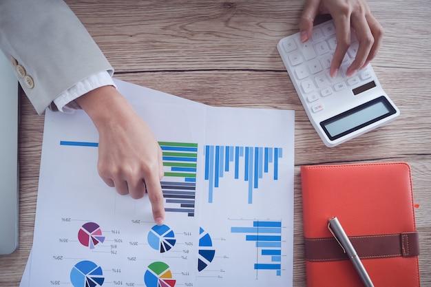 Concetto di contabilità aziendale, grafico indicante della penna dell'uomo di affari e facendo uso del calcolatore al bilancio calcolatore e carta di prestito in ufficio.