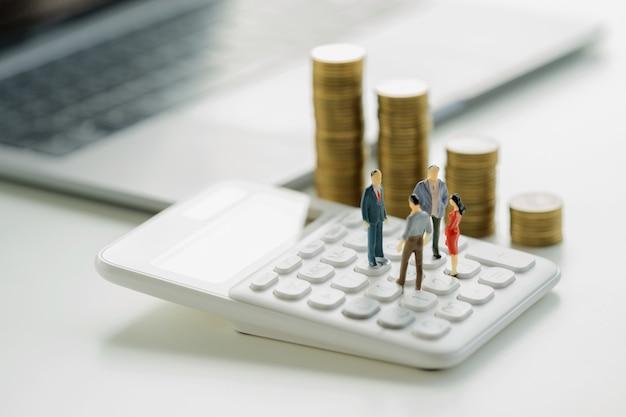 Concetto di contabilità aziendale. incontro giocattolo in miniatura sul calcolatore con pila di soldi