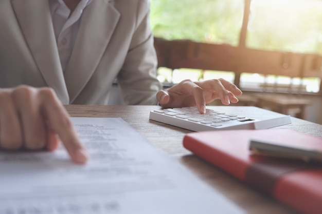 Concetto di contabilità aziendale, uomo di affari che utilizza calcolatore al bilancio calcolatore e carta di prestito nell'ufficio.