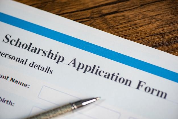Concetto di contratto del documento del modulo di domanda di borsa di studio con la penna per istruzione di concessioni