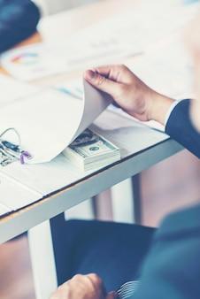 Concetto di corruzione e corruzione, tangente sotto forma di banconote da un dollaro
