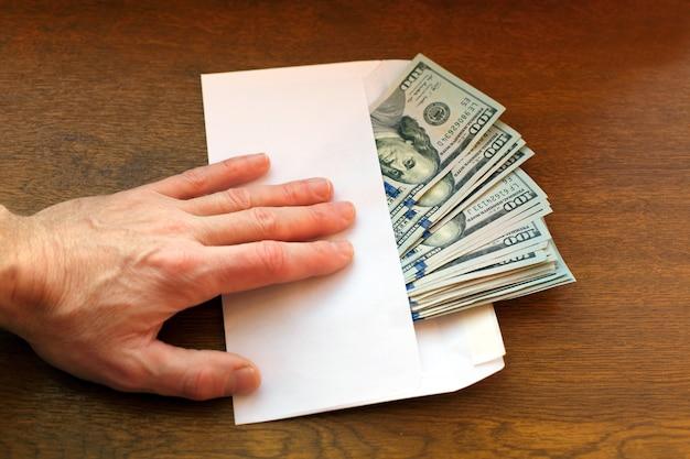 Concetto di corruzione. l'uomo d'affari prende una pila di soldi in busta.