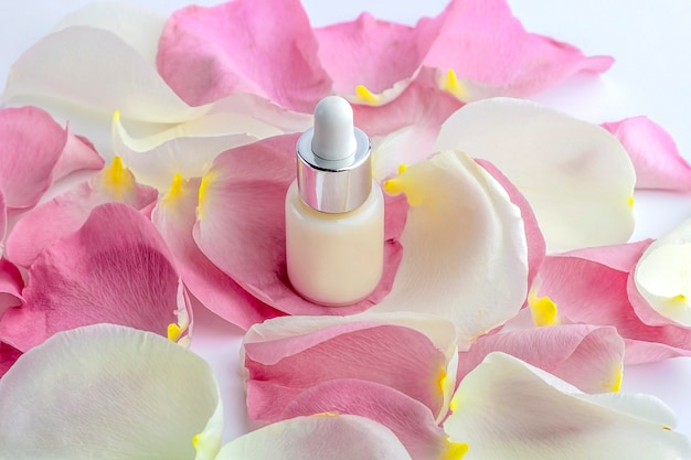 Concetto di cosmetici fatti in casa biologici naturali. cura della pelle, prodotti di bellezza: contenitori con siero viso tra delicati petali di fiori di rosa.