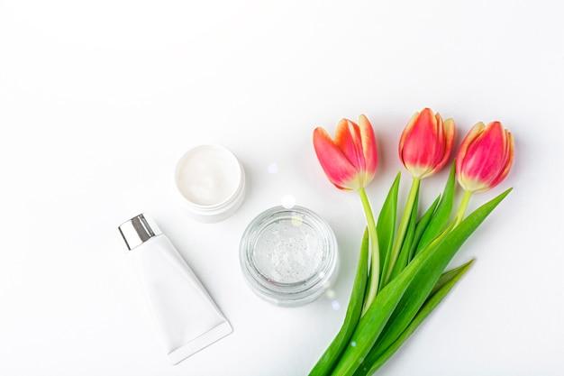 Concetto di cosmetici fatti in casa biologici naturali. prodotti per la cura della pelle, i rimedi e la bellezza: contenitori con crema e siero tra i fiori di primavera rosso tulipano laici piatti, copia spazio per il testo