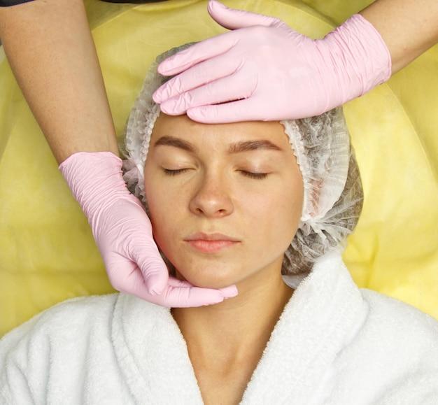 Concetto di cosmetologia. mani dell'estetista che puliscono e che toccano un fronte femminile con una spugna.