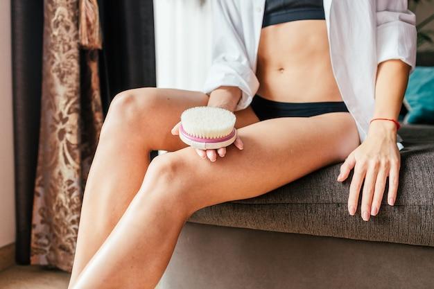Concetto di cosmetologia, toelettatura, anticellulite, esfoliazione e cura della pelle. donna esile del primo piano con la spazzola di legno morbida di massaggio per il corpo e le gambe. il fronte non è visibile.