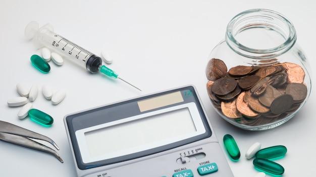 Concetto di costo di sanità, calcolatore, pinzette, compresse e siringa su priorità bassa bianca