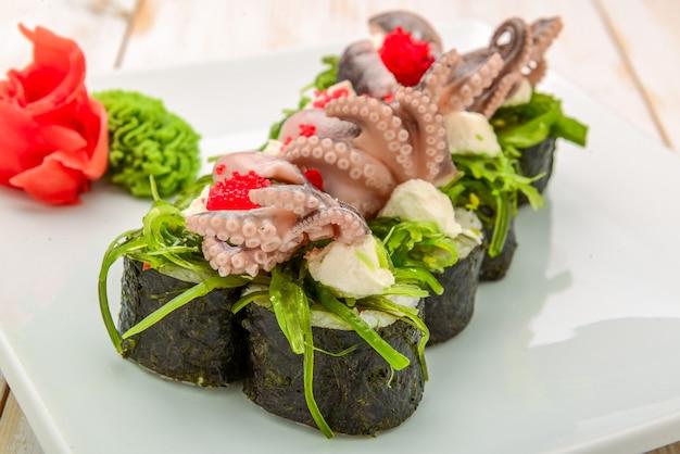 Concetto di cottura, asiatico della cucina, di vendita e dell'alimento - vicino su delle mani con le tenaglie che prendono i sushi al mercato di strada assortito dei sushi freschi
