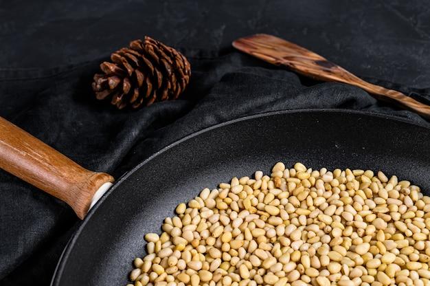 Concetto di cottura dei pinoli arrostiti in una padella. sfondo nero. vista dall'alto