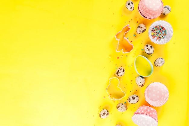 Concetto di cottura dolce per pasqua, sfondo di cottura con cottura - con un mattarello, frusta per montare, formine per biscotti, uova di quaglia, zucchero a velo