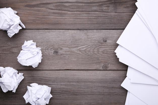 Concetto di creatività, carta stropicciata e foglio bianco su legno grigio