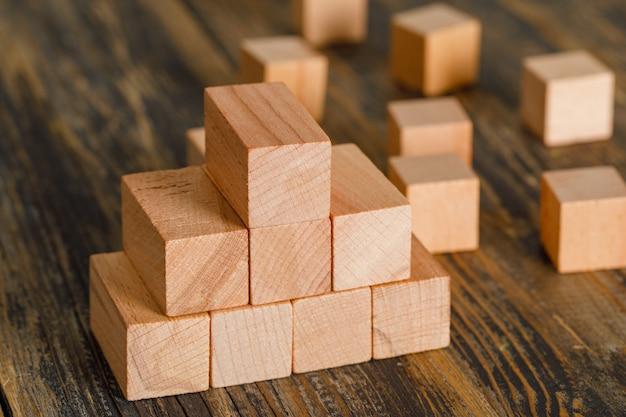 Concetto di crescita di affari con la piramide dei cubi di legno sulla vista di angolo alto della tavola di legno.