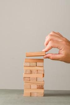 Concetto di crescita di affari sulla vista laterale della parete grigia e bianca. mano mettendo il blocco di legno sulla torre.