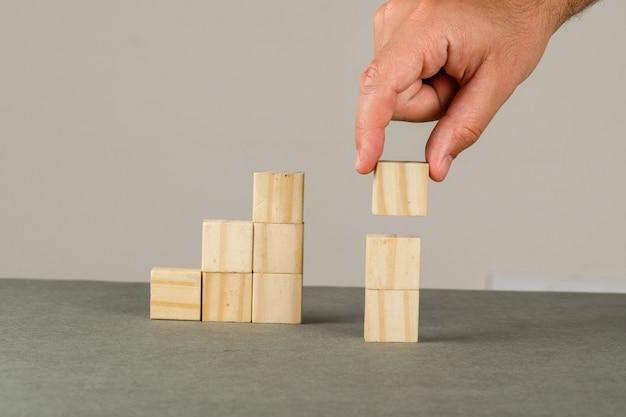 Concetto di crescita di affari sulla vista laterale della parete grigia e bianca. uomo che organizza il blocco di legno che impila la scala.