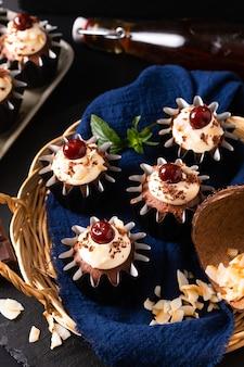 Concetto di cucina casalinga cupcakes crema di cocco foresta nera fatti in casa sul tovagliolo blu con spazio di copia