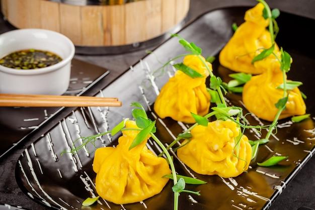 Concetto di cucina panasiatica. wontons di pasta gialla, carne macinata. gnocchi giapponesi con carne macinata. serve piatti nel ristorante su un piatto nero. spazio copia immagine di sfondo