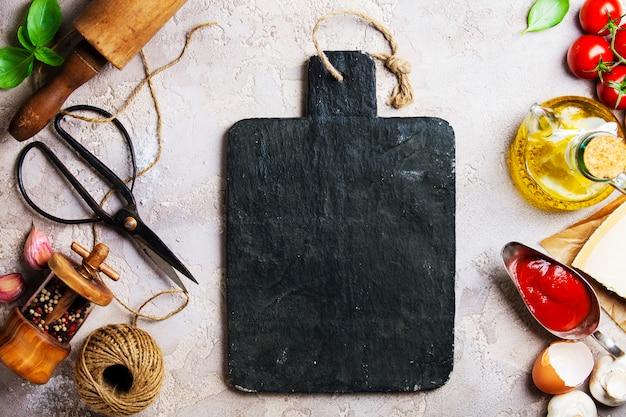Concetto di cucina, utensili da cucina e tagliere nero