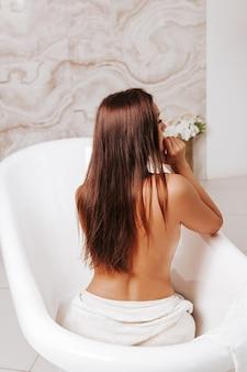 Concetto di cura del corpo. vista posteriore della giovane donna adulta che cattura bagno in un comodo bagno.