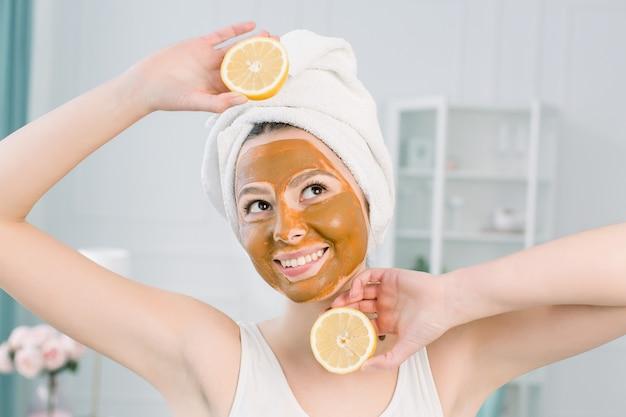 Concetto di cura della pelle di bellezza. la donna caucasica attraente in tovagliolo bianco con la mascherina facciale marrone sul fronte tiene gli agrumi sulla sua mano su spazio leggero. procedure della stazione termale e maschera crema sulla pelle