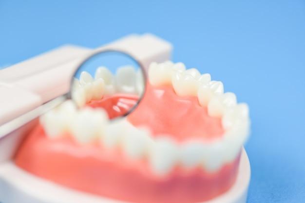 Concetto di cure odontoiatriche - strumenti del dentista con gli strumenti dell'odontoiatria delle protesi dentarie e controllo dell'igiene e dell'attrezzatura dentale con salute orale del modello dei denti e dello specchio della bocca
