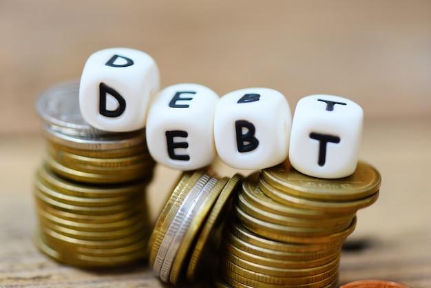 Concetto di debito con il debito del blocco e le monete impilate sul fondo di legno della tavola