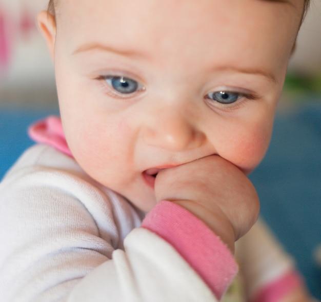 Concetto di dentizione. bambina con il dito in bocca.