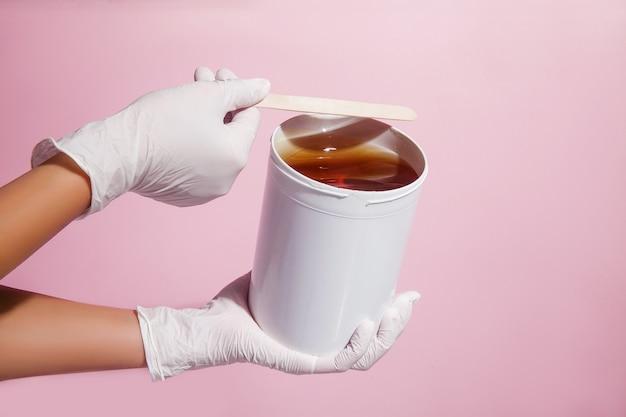 Concetto di depilazione e depilazione. chiuda sulle mani del `s di medico in guanti e l'uniforme dell'abito medico con la pasta dello zucchero