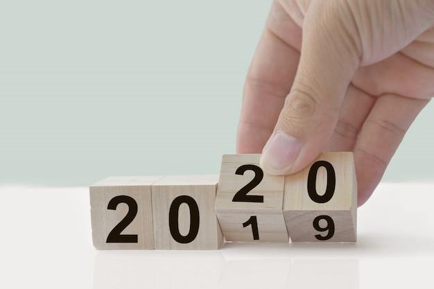 Concetto di design: il nuovo anno 2019 cambia in 2020, cambia a mano i cubi di legno sul tavolo bianco.